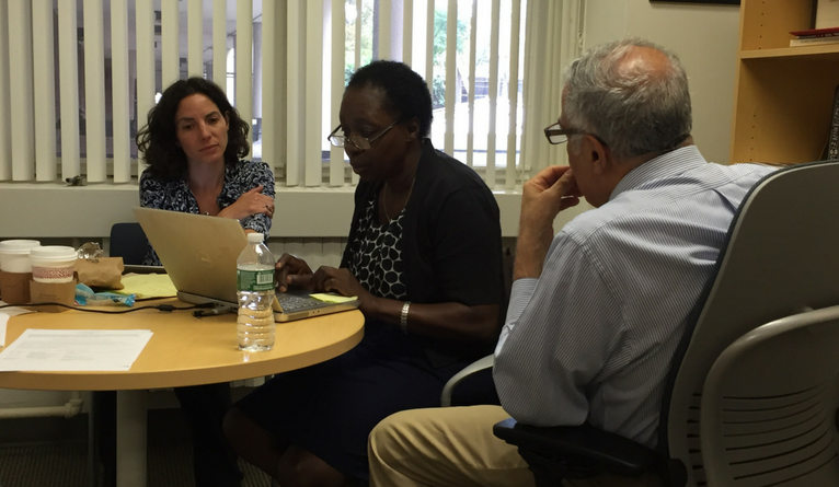 Tracy Rabin, Harriet Mayanja-Kizza, and Asghar Rastegar working in Dr. Rastegar's office at the Yale School of Medicine.